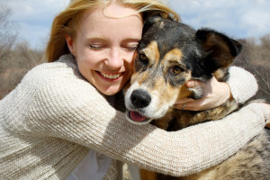 woman-hugging-dog-outside