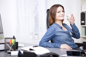 woman-at-office-drinking-glass-water