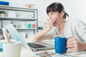 woman-at-desk-coffee-yawning-fatigue