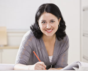 woman-at-desk-writing-smiling