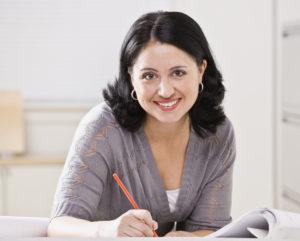 woman-at-desk-writing-smiling