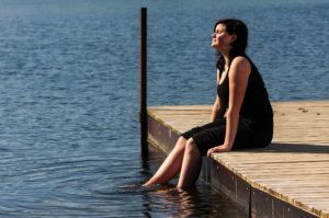 woman-on-dock-legs-in-water