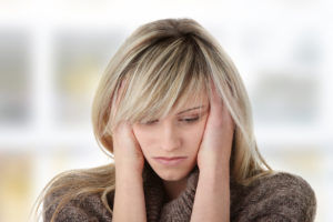 Stressed woman with her head between her hands.