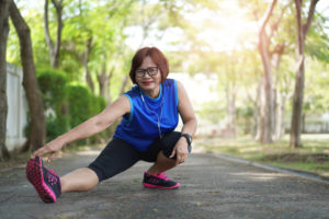 Senior asian woman stretch muscles at park and listening to music. Athletic senior exercising together outdoor. Fit senior runners stretching before running outdoors.