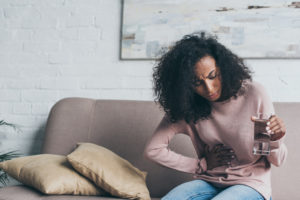 woman sitting on the couch with abdominal pain