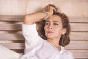 dramatic lifestyle portrait of attractive sad and depressed middle aged around 50s woman feeling upset alone on bed suffering depression and anxiety crisis as mature lady lost and confused