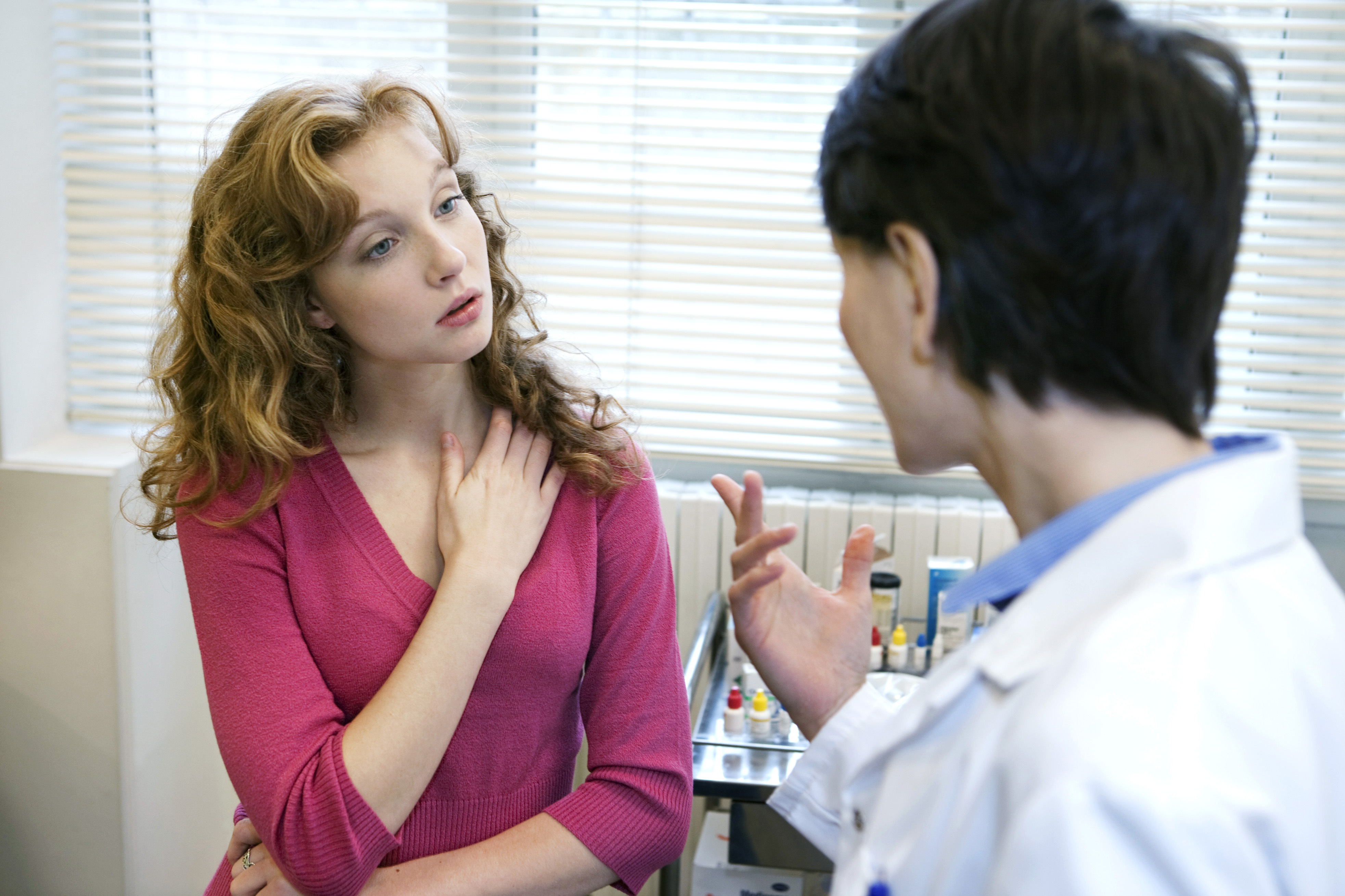 Woman with red hair and pink shirt talks to a doctor