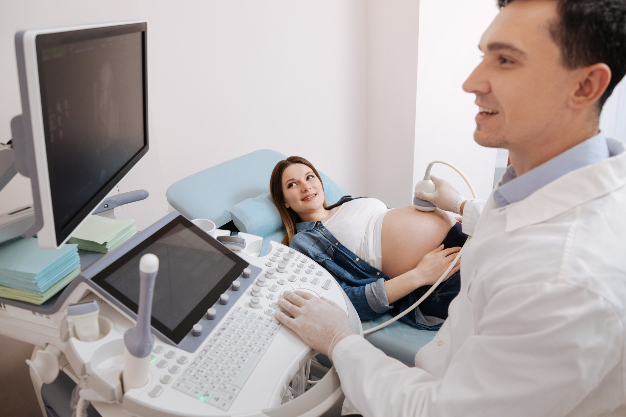 obstetrician working in the hospital while performing an ultrasound of pregnant belly, monitoring and consulting pregnant patient