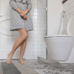 Woman with urinary problem in front of toilet bowl. Lady clenching her hands holding her pee.
