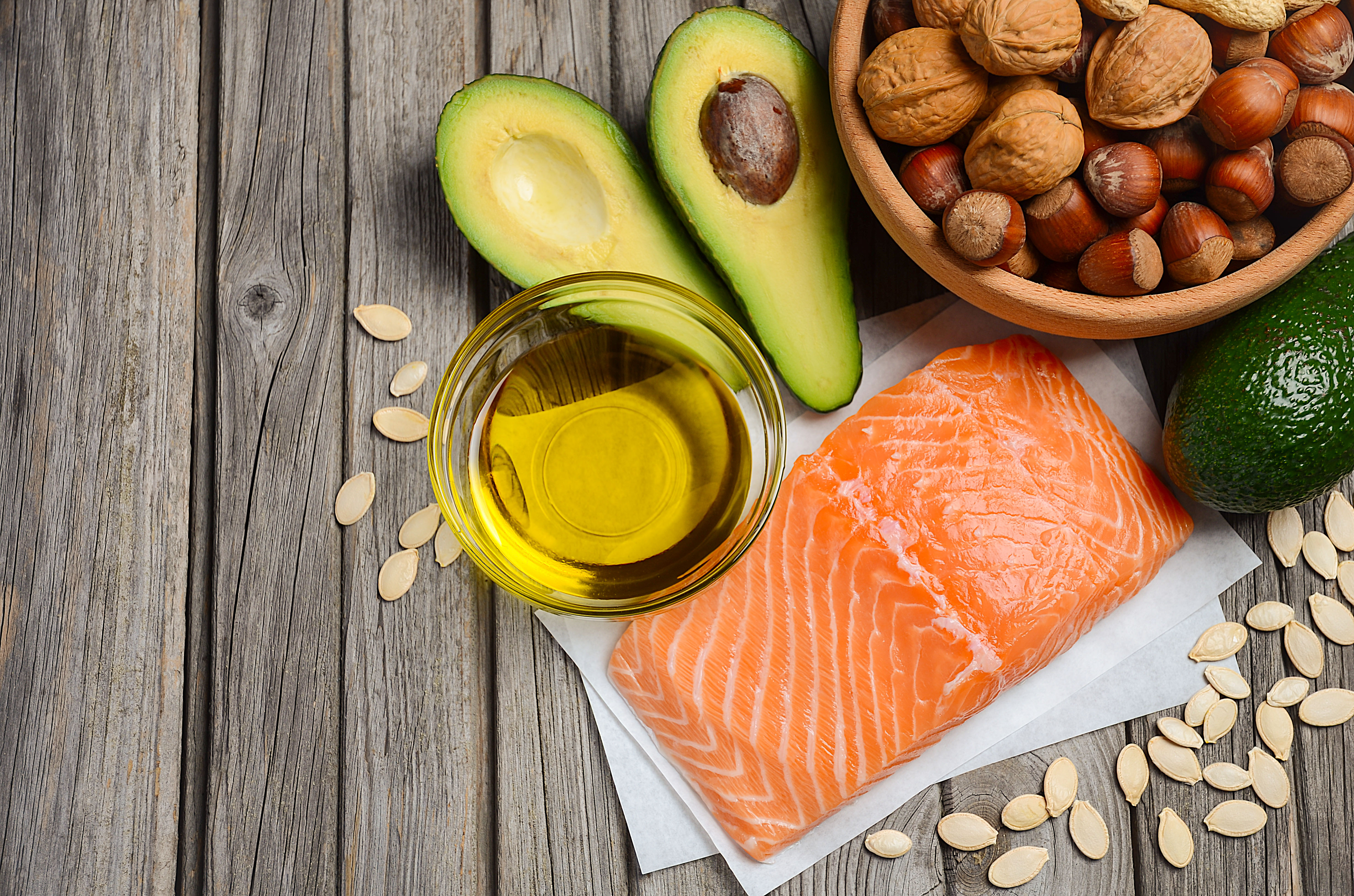 picture of olive oil, salmon, avocado and a bowl of nuts