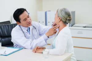 Doctor checking thyroid glands of senior woman