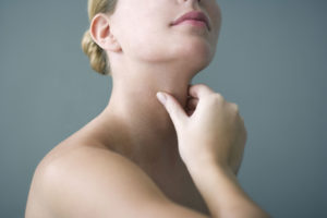 woman holding her thyroid