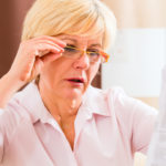 woman reading prescription side effects with an open mouth, holding her glasses with one hand