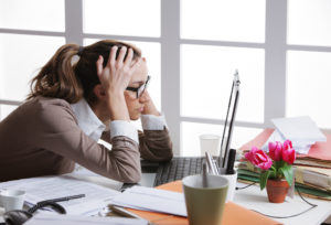 businesswoman tired from work in the office holding her head