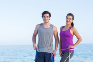 Smiling couple measuring their waist at the beach
