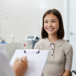 Waist up portrait of Asian teenage girl looking at doctor and smiling happily during consultation in doctor's office